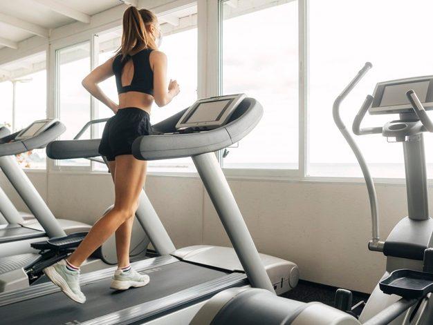 kvinde løber på løbebånd